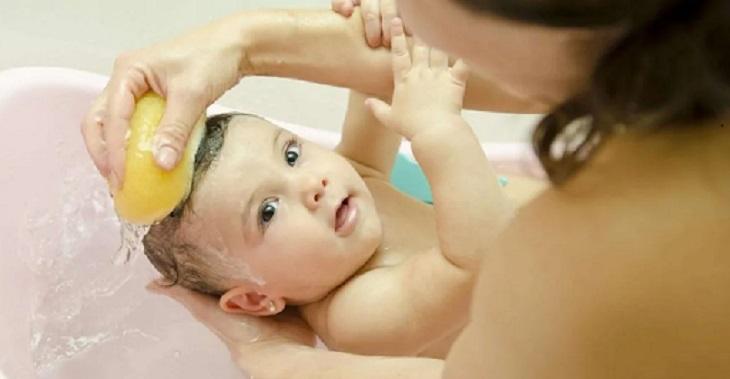 Dùng lược hoặc bông tắm xoa vùng bị viêm da tiết bã ở trẻ sơ sinh giúp vảy bong nhẹ nhàng